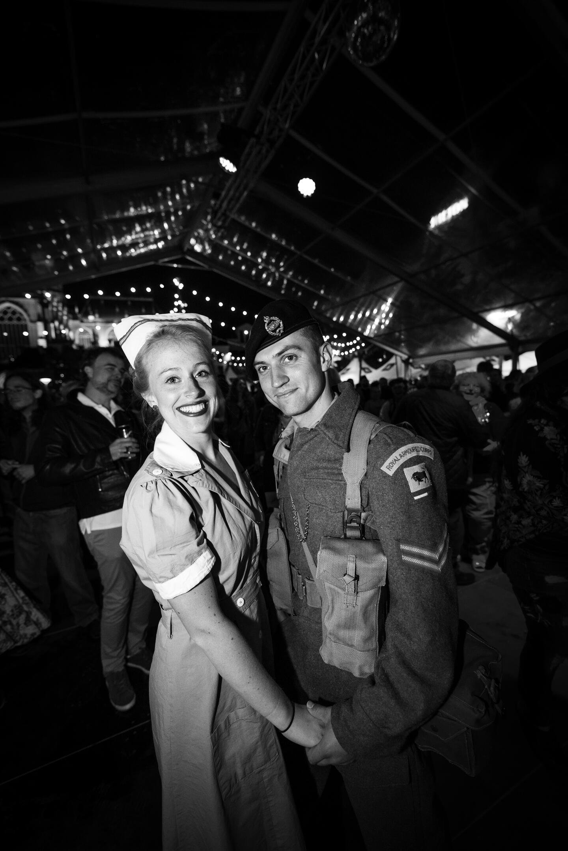 Vrouw en man in soldatenuniform poseren op een feest.