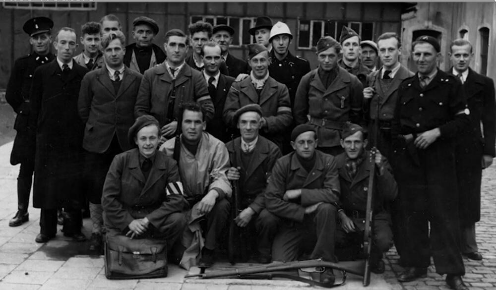 Een groep mensen poseert op een zwart-witfoto.