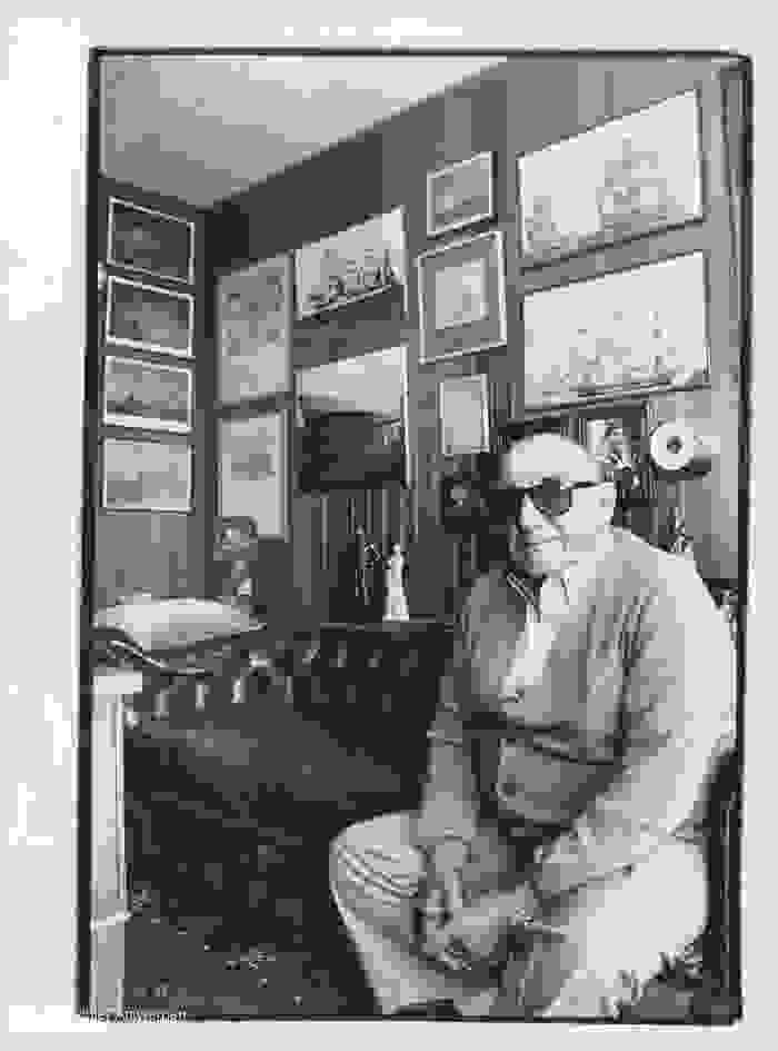 Eugène Colson op een sofa met een muur met kaders achter zich