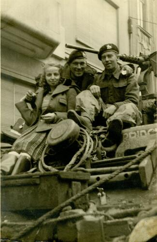 Jonge vrouw en twee soldaten op een tank