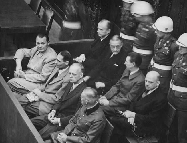 Mannen zit in 2 rijen in de beklaagdenbank. Achter hen staat een rij soldaten.