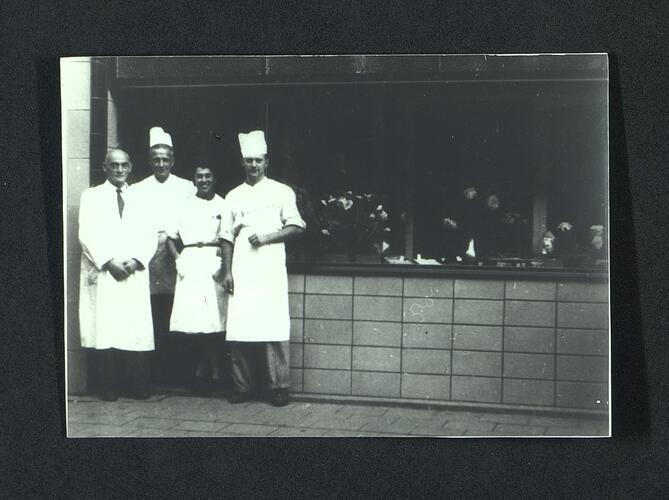 Medewerkers van een bakker poseren voor de gevel.