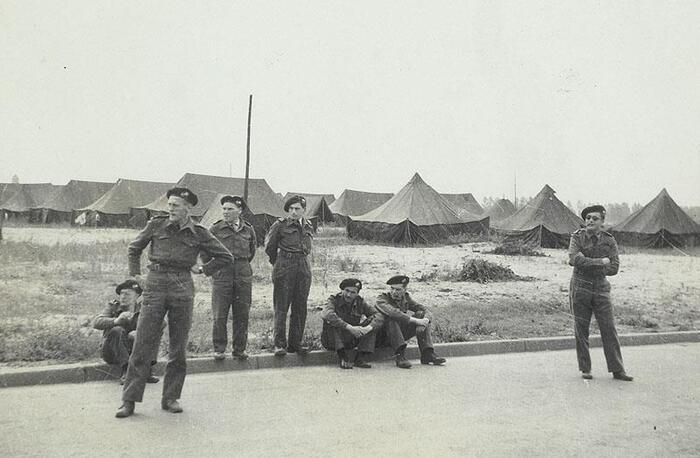 Soldaten wachten en staan aan de kant van de weg. Op de achtergrond staan tenten.