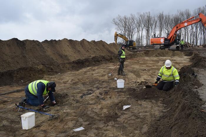 Drie mensen voeren opgravingen uit. Op de achtergrond staat een kraan.