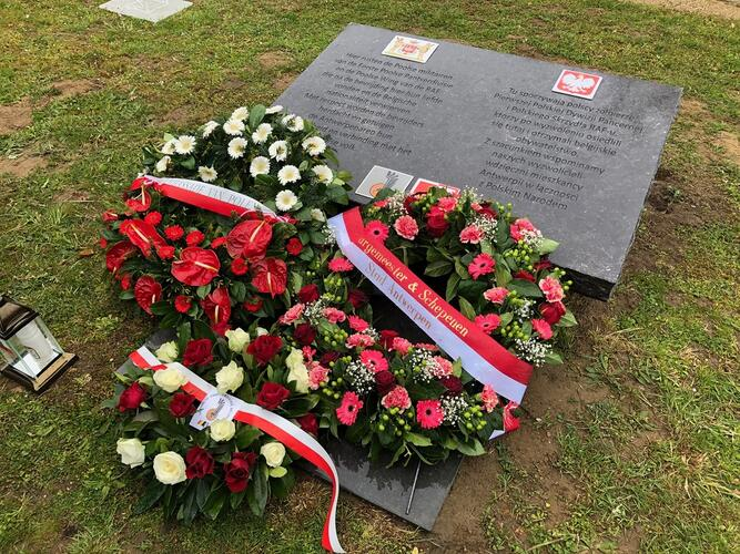 Bloemenkransen bij een gedenksteen