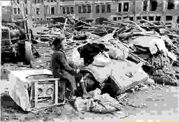 Een vrouw zit op een apparaat tussen het puin na het bombardement op Mortsel